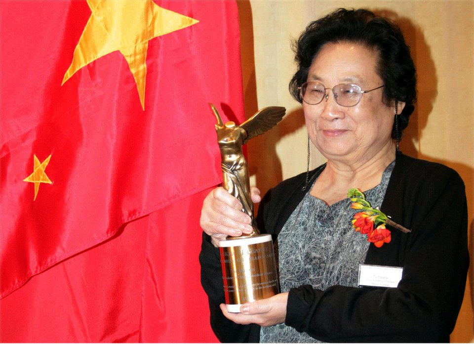 This photo released by the Xinhua News Agency October 2015 and is taken 23 sep, 2011. Chinese pharmacologist Tu Youyou poses with his trophy after winning the Lasker Award, a prestigious medical prize awarded in New York, USA.